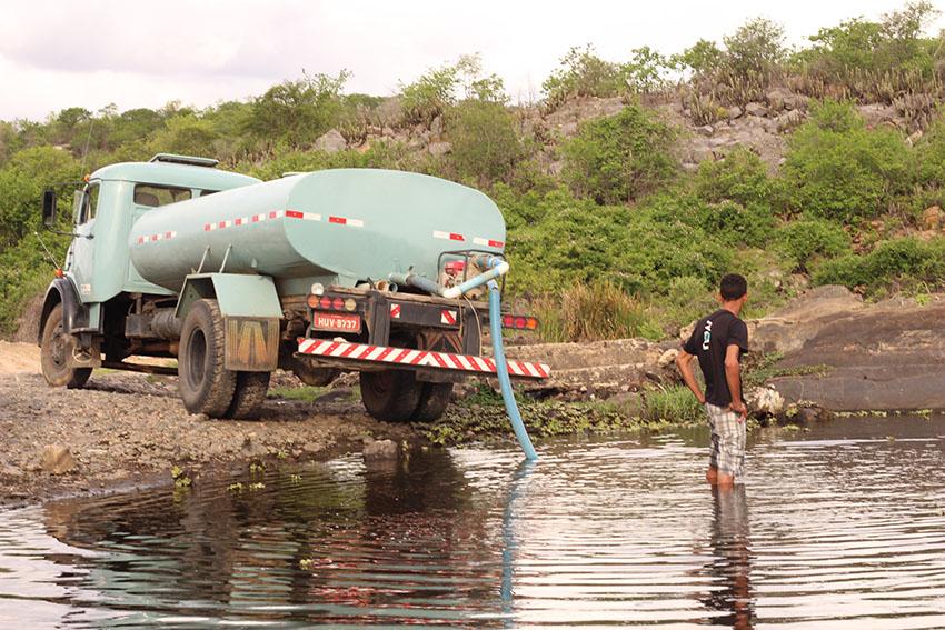 Carros-pipa tiram água da pouca água que desce no rio Banabuiú. (Foto: Jéssica Welma/Tribuna do Ceará)
